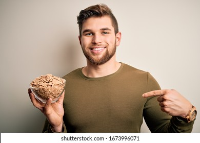 Young blond man with beard and blue eyes holding bowl with cornflakes cereals with surprise face pointing finger to himself