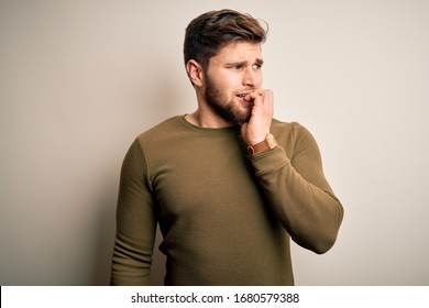 Young blond man with beard and blue eyes wearing green sweater over white background looking stressed and nervous with hands on mouth biting nails. Anxiety problem.