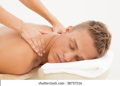 Young blond man enjoying massage session in spa resort