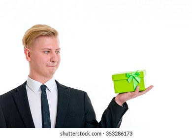 young blond man with green gift in front of white background