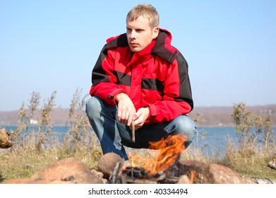 Young blond man in red weatherproof jacket (windcheater, windbreaker) sit near fire on the seashore.