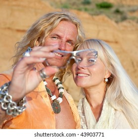 Young blond man and blond woman  are looking  at camera through a sunglasses