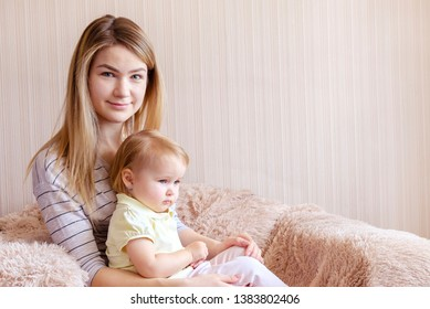 Young blond mother and her daughter child sitting in armchair at home and looking away. Copy space