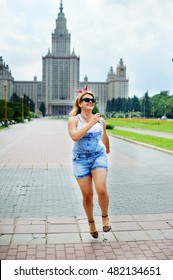 Young blond plus-size woman in the park on beauty summer day