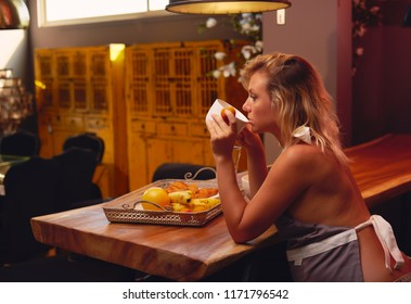 Young blond pregnant woman wearing cover-slut sitting and drinking a tea, coffee in kitchen at home alone