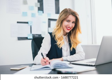 young blond smiling businesswoman works in her laptop in modern office, taking notes to her business planner,looks confident and busy, multitasking, work concept
