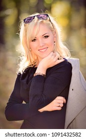 A young, blond and smiling woman portrait on a sunny autumn day.