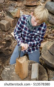 Young blond timberjack trimming firewood with an axe
