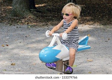 A young blond toddler girl with sunglasses, rides on a toy bomb or missile at a park with a serious expression concentrating on making it go.