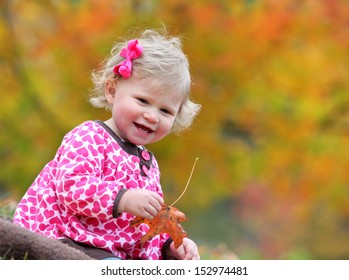Young blond toddler playing with leaf in fall