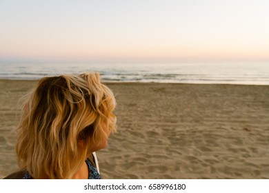 young blond woman in beach at sunset looking at sea