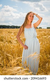 Young blond woman in a blue dress. A girl stands in the middle of a wheat field on a sunny day. Field, wheat, beauty, nature, relaxation - The concept of country vacation. Article about vacation.