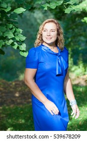 Young blond woman in blue dress standing in the autumn park