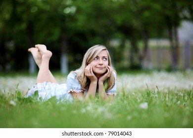 Young blond woman in blue dress in the park