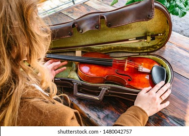 Young blond woman in brown coat taking classic wooden shiny violin from a leather case to play on wooden rustic table on cafe terrace outside on sunny day. Music, arts and hobby concept