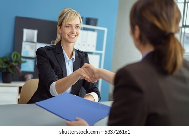 Young blond woman in a business employment interview shaking hands with the manageress or personnel officer who is holding her CV