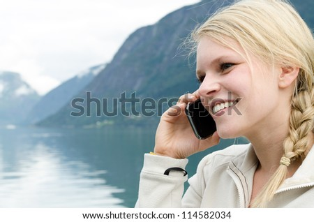 young blond woman called up with her Smartphone with a fjord in Norway in the background