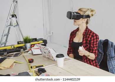 Young blond woman in casual clothes sitting at wooden workbench with tools and laptop and enjoying virtual reality experience in goggles headset holding joystick in hand.