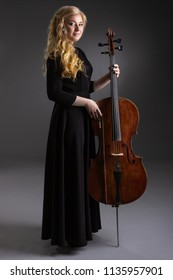 Young blond woman with cello on a dark background.