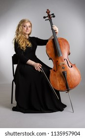 Young blond woman with a cello on a light background.