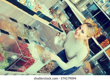 Smiling young blond woman choosing dried berries sold by weight in organic boutique