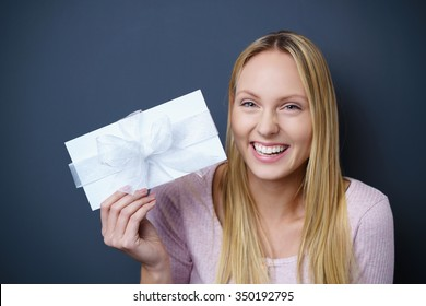 young blond woman displaying an envelope tied with a festive white ribbon and bow, conceptual of love or an award or prize