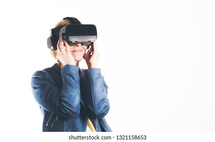 A young blond woman dressed in modern glasses works in a virtual reality on a white background. The future is now. Modern technologies for work, study, travel, communication, games
