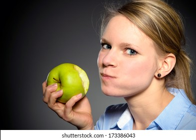 young blond woman eats joyfully a green apple