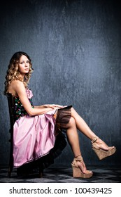 young  blond woman in elegant pink dress sit on chair in empty grunge room with tiled floor