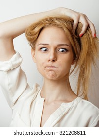 young blond woman emotional in studio isolated gesturing, making goofy faces