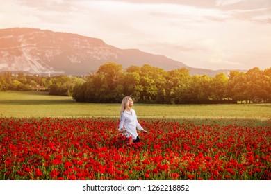 Young blond woman enjoying amazing view of poppy field, Saleve mountain, image taken in Geneva, Switzerland