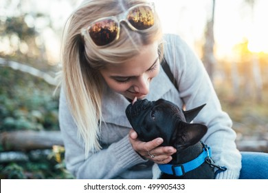 Young blond woman enjoying with her french bulldog puppy in sunny day. Selective focus.