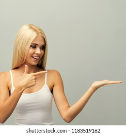 Young blond woman in fitness wear, sitting on floor, giving or showing something, or copyspace area for text, slogan, advertising, against grey wall.