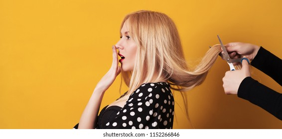 Young blond woman has cutting her long hair in hairdresser. Scissors cut the girls hair. Concerned woman with anxious expression cutting off her hair, over yellow wall. Time to change hairstyle