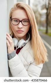 Young blond woman with headphones standing outside looking serious