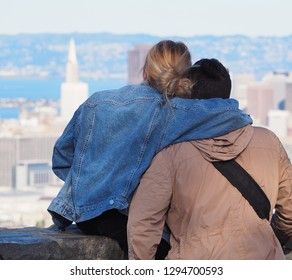 Young blond woman holding boyfriend, looking together at the city of San Francisco, with the Transamerica Pyramid in background