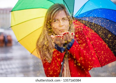 young blond woman holding rainbow color umbrella in a festive mood on a rainy day. blowing glitter confetti