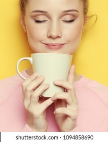 Young blond woman holding white cup with tea or coffee, lifestyle and food concept.