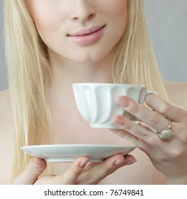 Young blond woman holding white tea cup