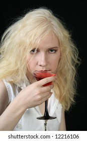 Young blond woman holds martini against the black background
