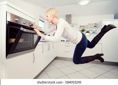 Young blond woman in the kitchen levitating