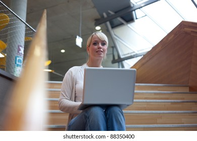 young blond woman with a laptop on the stairs/ woman with laptop