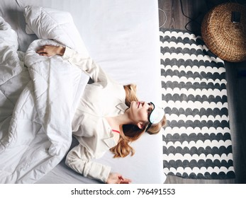 Young blond woman laying in bed. Female in pajamas. Sleeping, resting, holiday season. Top view.