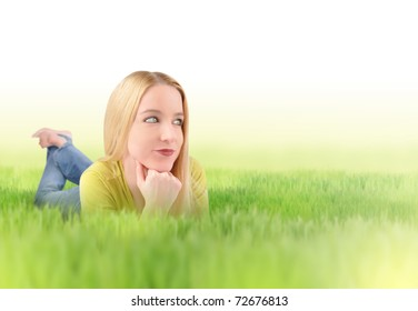 A young blond woman is laying in the grass looking up in the sky. There is white copyspace to add your message. Use it for an environment or green concept.