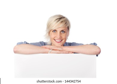 Young blond woman leaning on white sign against white background