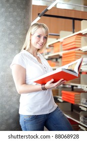 young blond woman in a library with a book/blond woman in a library