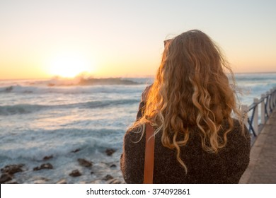 A young blond woman with long wavy hair and sunglasses taking a picture at the west coast of Fuerteventura, Spain