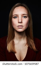 Young blond woman is looking seriously and head-on at the camera against a dark background