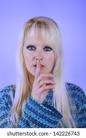 Young blond woman making silence finger over her mouth