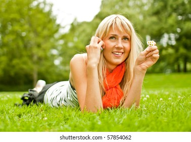 Young blond woman with mobile phone in the park